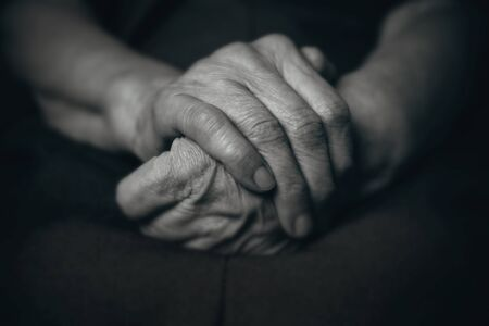 senescence: Two hands of an old man on a dark background