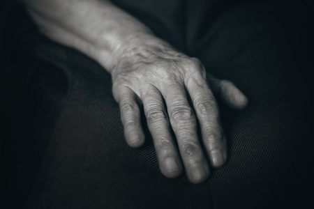 oldness: Old mans hand on a dark background