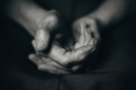 senility: Two old mans hands on a dark background
