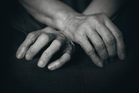 senescence: Fingers of the old mans hands in his lap Stock Photo