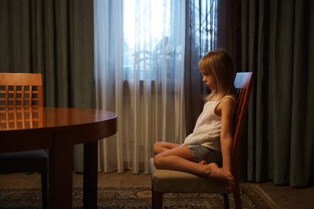offended: Offended little girl sitting on a chair Stock Photo