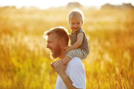 blessedness: Happy father carries his son on shoulders