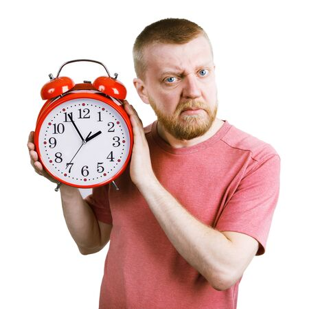 exasperation: Unhappy bearded man with a red alarm clock in his hand