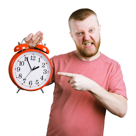 exasperation: Disgruntled man holding a big red alarm clock