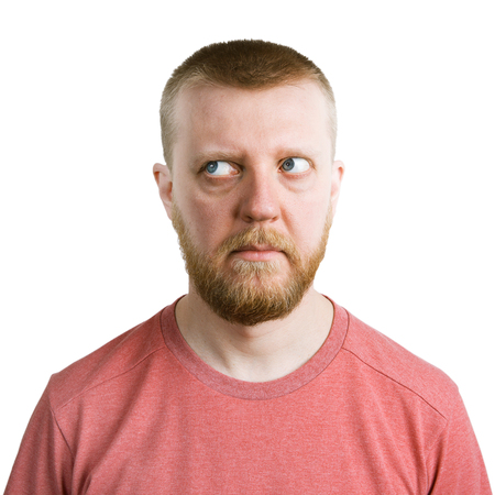 aside: Bearded man looking eyes away from himself Stock Photo