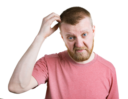 bloke: Young bearded man scratches his head hair Stock Photo