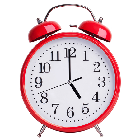five to twelve: Red alarm clock shows exactly five oclock