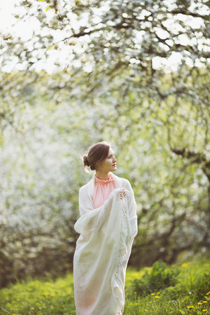 beatitude: Happy young woman stands in the middle of a blossoming garden Stock Photo
