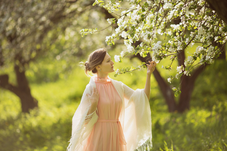 beatitude: Happy young woman near the blossoming apple tree Stock Photo