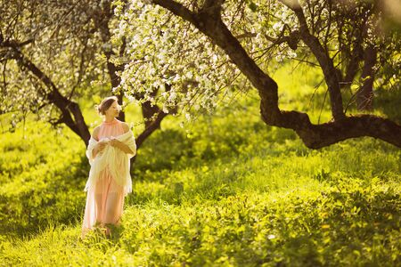 beatitude: Happy beautiful young woman smelling a flower on an apple tree