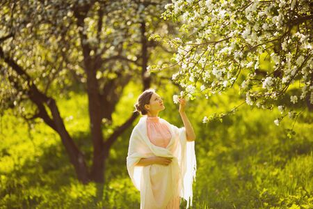 pacification: Happy beautiful young woman smelling a flower apple