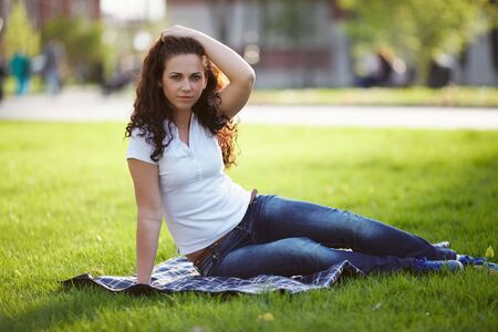 blessedness: Beautiful young woman in jeans sits on the grass Stock Photo