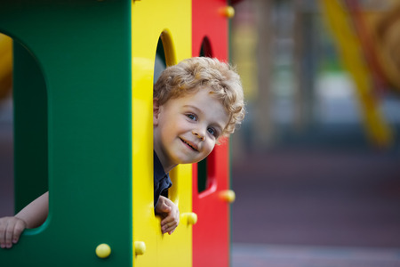 lurk: Small curly boy is hiding in the playground
