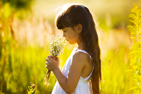 blessedness: Little girl with a bouquet of wildflowers Stock Photo