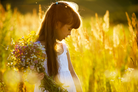 blessedness: Little girl with a bouquet of wild flowers Stock Photo