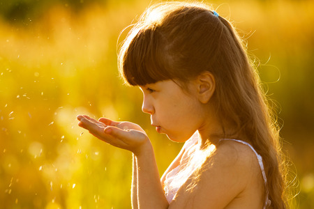 girlie: Little girl blowing on seeds in the palms