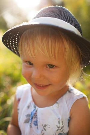 honey blonde: Little blonde smiling girl in a blue hat