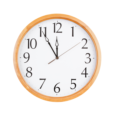 12 hour: Round office clock shows five minutes to twelve