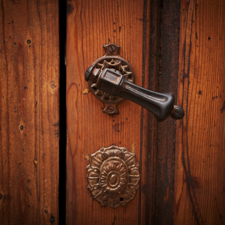 door handle: Ancient door handle on a wooden door