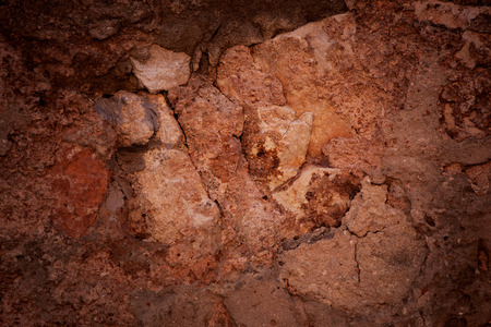 hardwearing: Red and brown rough stone surface with cracks Stock Photo