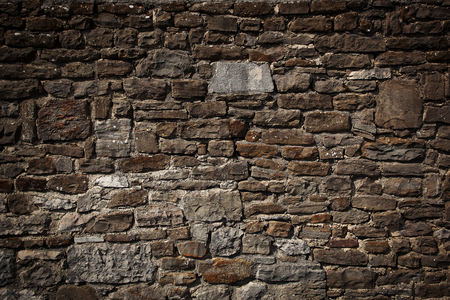 firmness: Ancient brown wall made of different sizes stones Stock Photo
