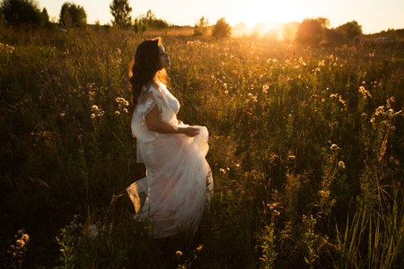 Girl in a white dress walks in the evening on the field