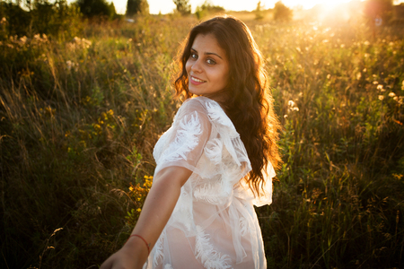 Girl in a white dress walks in the field at sunset Banque d'images
