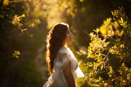 Beautiful woman in the garden at sunset