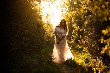 Beautiful young woman in a white dress at sunset Banque d'images