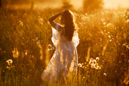 Girl in a dress stands in the field at sunset Banque d'images