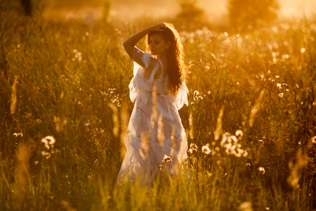 Woman in a dress standing in the field at sunset