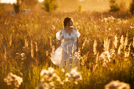 Girl in a dress walks through a meadow at sunset