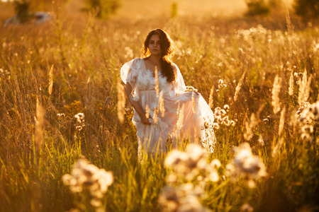 Bride walks through the meadow at sunset