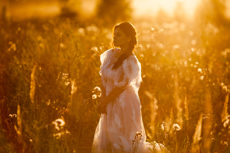 Beautiful woman walking in the meadow at sunset