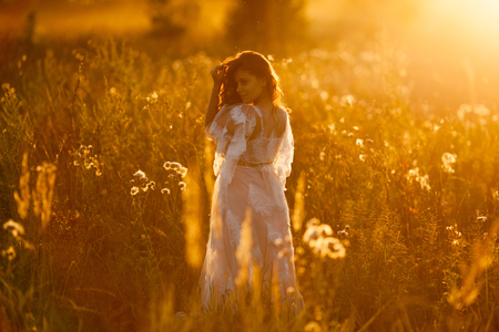 Beautiful girl walking in the meadow at sunset