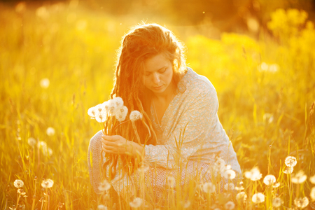 Girl in dreadlocks with a bouquet of dandelions