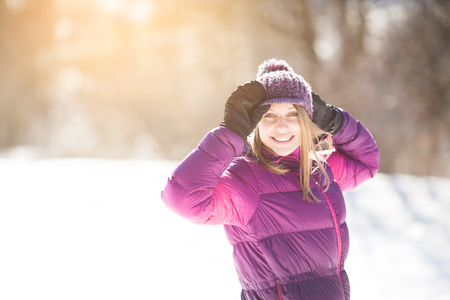 Happy young woman in mittens and hat