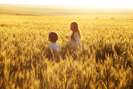 Happy mom and son run through a field of rye in the rays of the evening sun Banque d'images