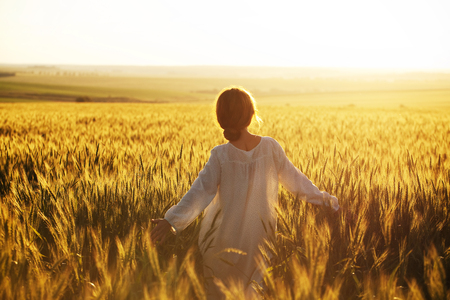 Happy woman walks over wheat field in the rays of the evening sun