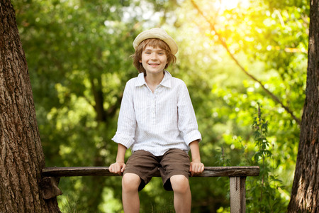 Cheerful boy in pajamas sits in the forest on a bench