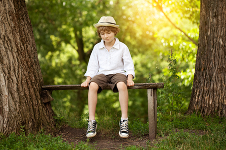 Boy in shorts and a hat sits on a bench Stockfoto