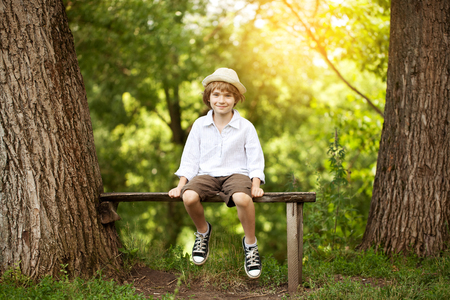 Cheerful boy in a light hat sitting on a bench