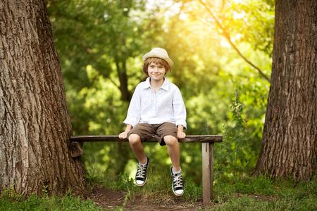 Vrolijke jongen in een lichte hoed zittend op een bankje