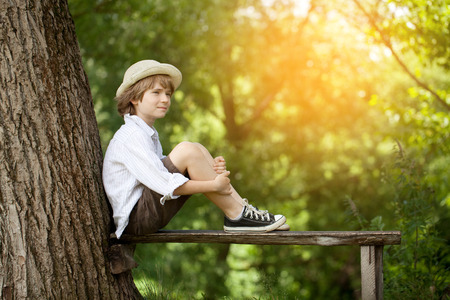 Boy in the light hat is sitting on the bench Stockfoto