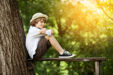 Boy in shorts and a hat sits on a bench