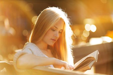 Schönes Mädchen sitzt und liest ein interessantes Buch