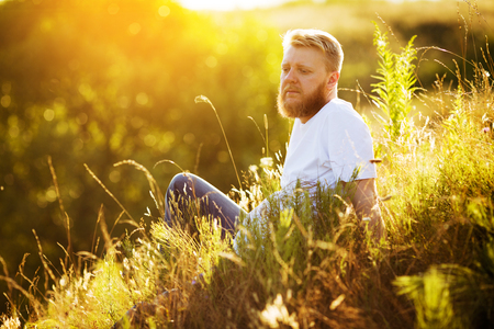 Happy bearded guy resting among wildflowers in summer 写真素材