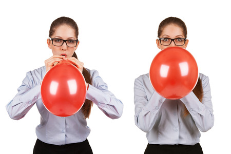 Girl with glasses inflates a red ball