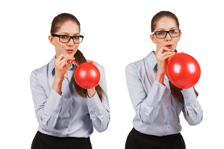 Playful girl with glasses inflates a red balloon Banco de Imagens