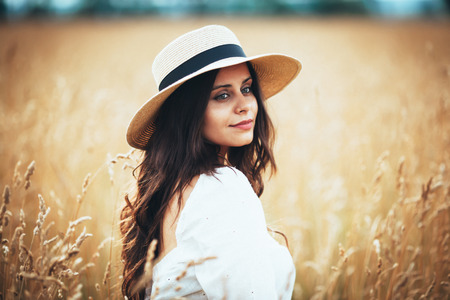 Beautiful young woman in straw hat among field grass Banque d'images